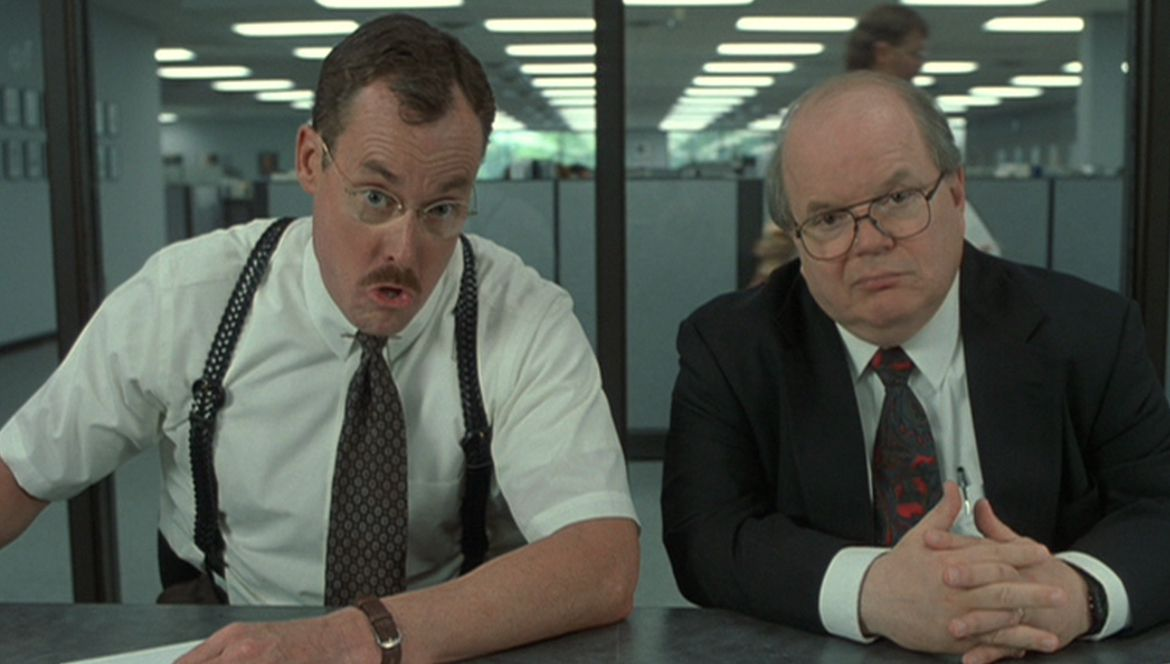 Two consultants in office space, both white men. One of them is John C. McGinley