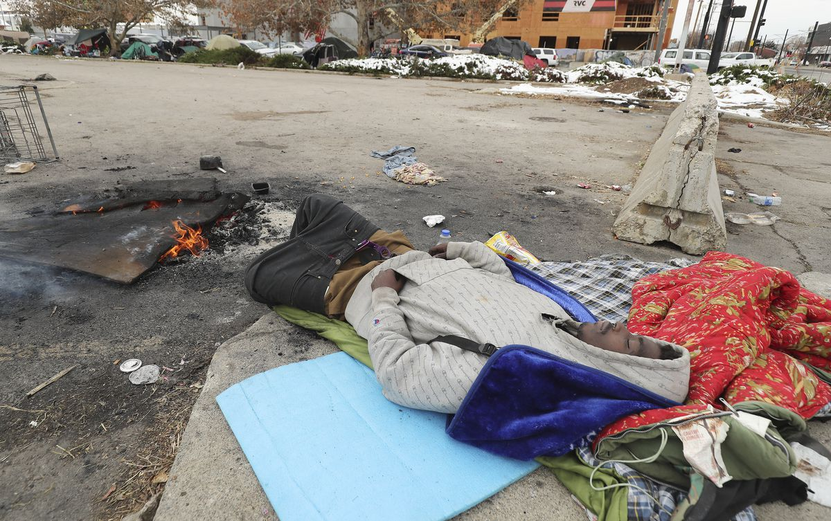A homeless man sleeps on 700 South in Salt Lake City on Tuesday, Nov. 10, 2020. The Kem C. Gardner Policy Institute on Tuesday published a report identifying major problems within the state's current homeless governance structure.