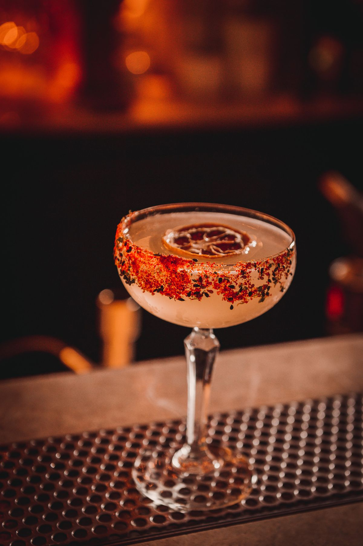 A deep red photo of a margarita with red salt on the rim, at a bar.