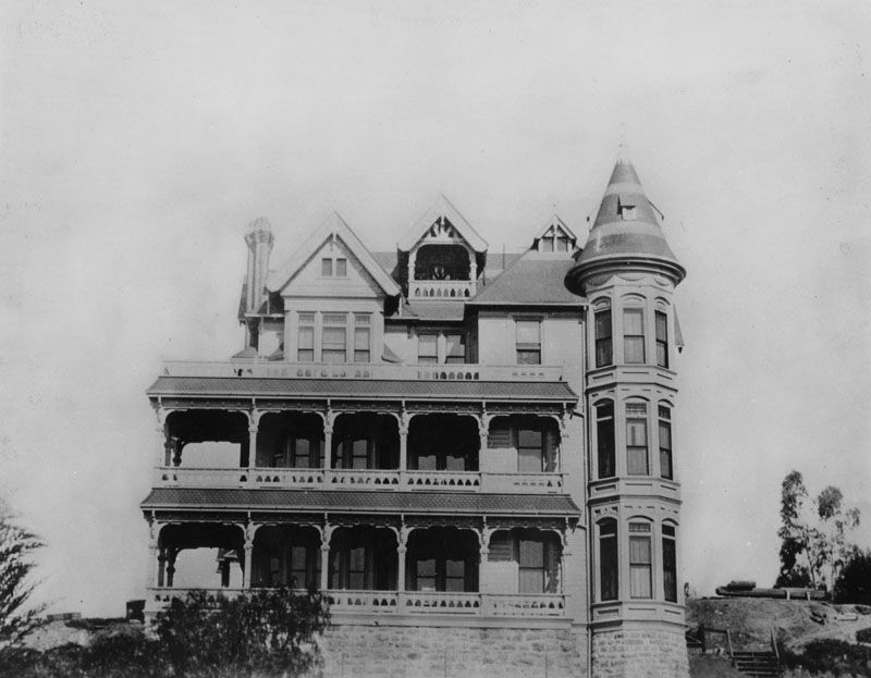 A large mansion with multiple floors and towers. There are balconies on two of the floors.