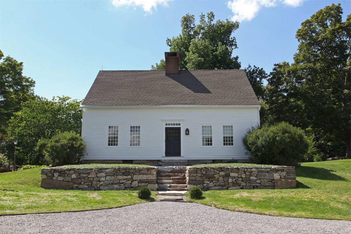 A simple, white, open gable home with center chimney sits on manicured lawn with stone steps leading to the front.
