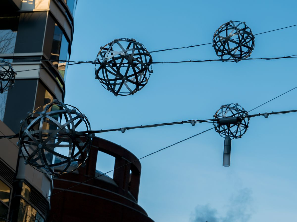 Unlighted lights suspended on wires above an urban setting.