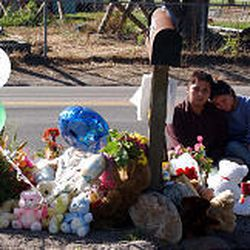 Eddy Robles, left, and Bridgitte Sierra sit in front of a memorial at the busy roadside by the driveway where Eddy Robles' niece and nephew died.
