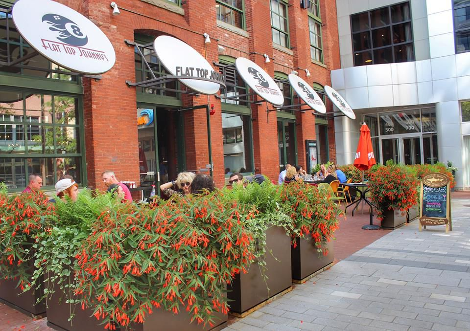 A small restaurant patio is bordered by flower boxes and sits in front of the restaurant's main entrance. Window awnings feature a pool eight ball logo.