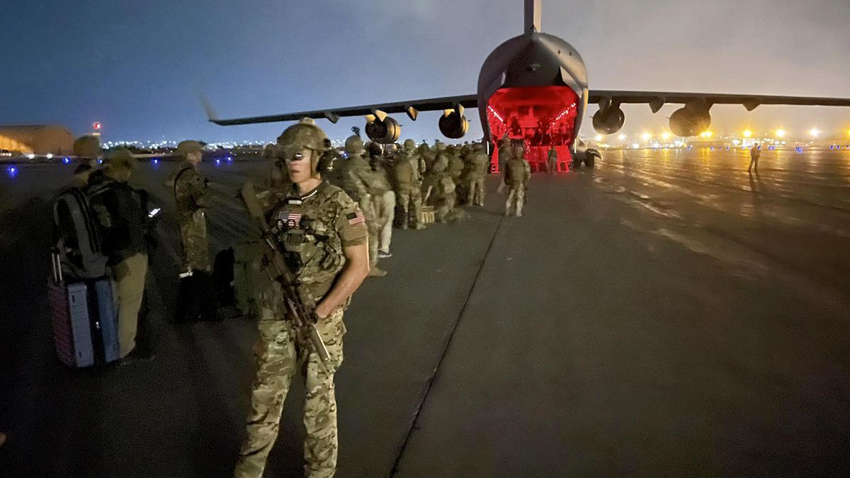 Paratroopers assigned to the 82nd Airborne Division, and others, prepare to board a C-17 cargo plane in Kabul, Afghanistan.