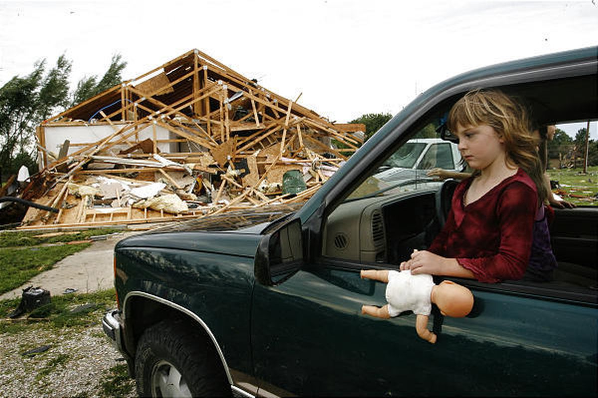 Chandrajo Ushman, 5, sits inside her father's truck after winds destroyed her home in Loami, Ill., on Wednesday. Twelve homes were destroyed and another 12 were damaged in the town. Tornadoes also were reported in  Wisconsin, Minnesota and Iowa.
