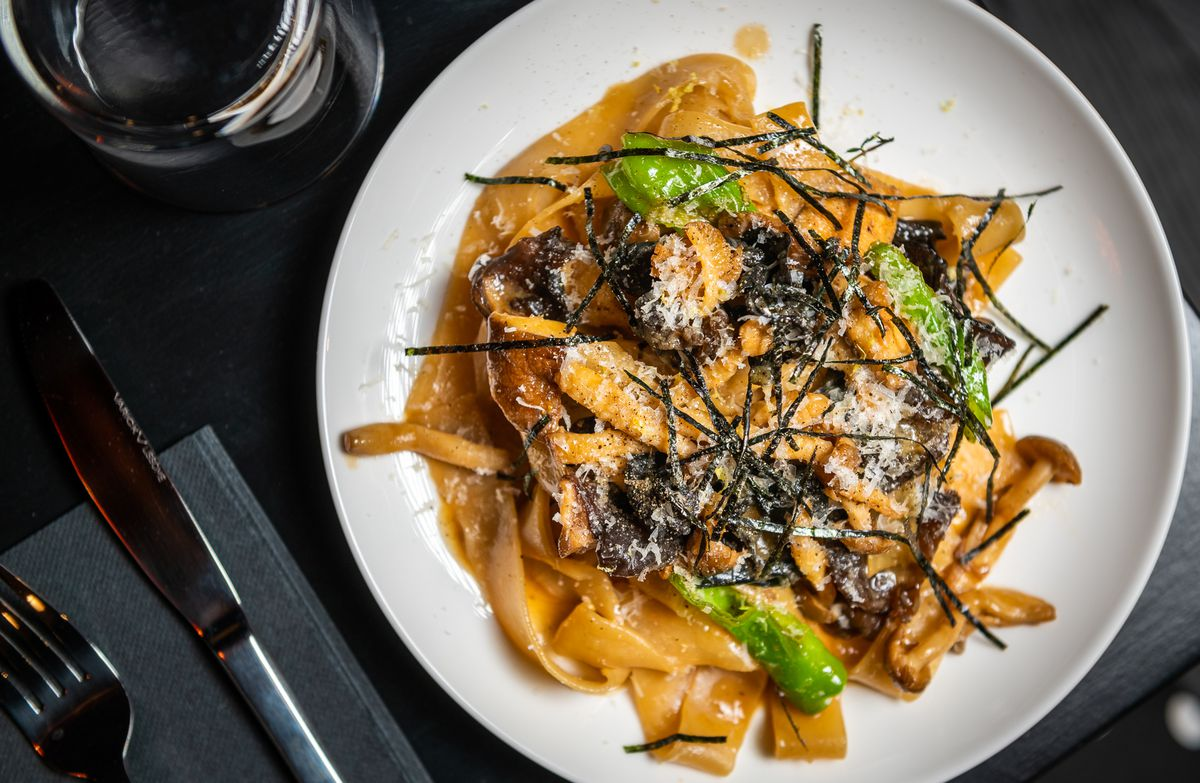 A plate of Japanese mushroom and shishito pepper pappardelle at Tonari gets garnished with pecorino cheese and nori.