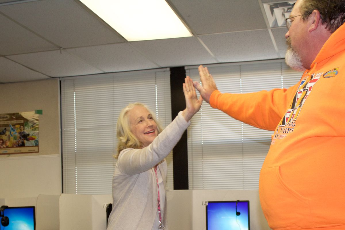 Two teachers high-five during an activity as part of their Beyond Textbooks training at Rose Hill Elementary on April 28, 2017. (Photo by Yesenia Robles, Chalkbeat)