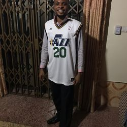 Ghanaian Dennis Agyekum, an Abomosu coach, teacher and sports director, is all smiles in his white Gordon Hayward jersey.