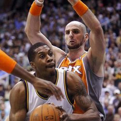 Utah Jazz forward Derrick Favors (15) works to get a shot up with Phoenix Suns center Marcin Gortat (4) defending as the Utah Jazz and the Phoenix Suns play Tuesday, April 24, 2012 in Energy Solutions arena.