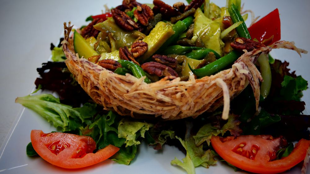 """A fried taro """"bird's nest"""" is full of vegetables, walnuts, and more, sitting on a bed of lettuce, with tomato slices, on a plate."""