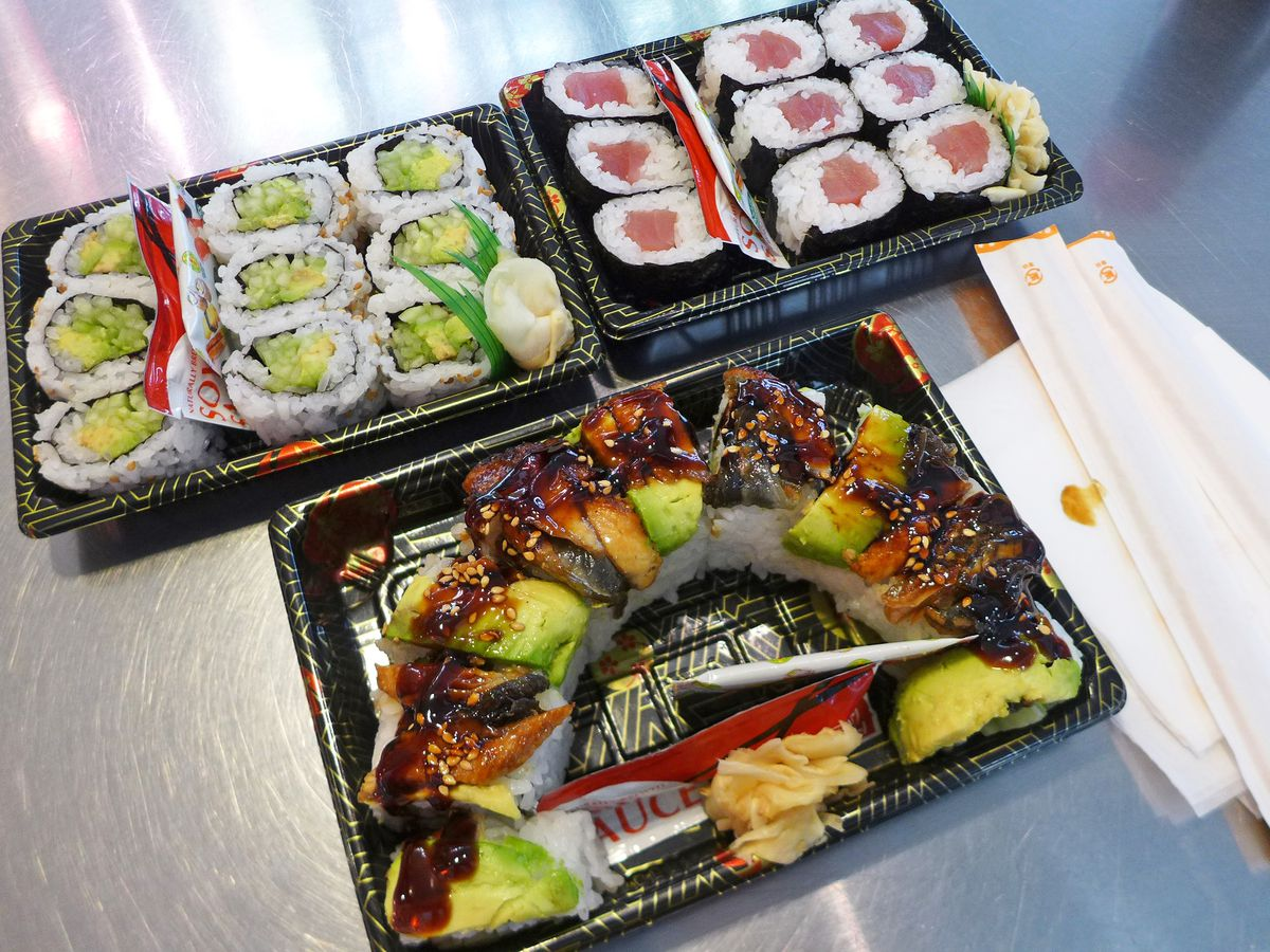 Three boxes of sushi package for carryout including a dragon roll with eel and avocado and dribble with dark syrup in the foreground.