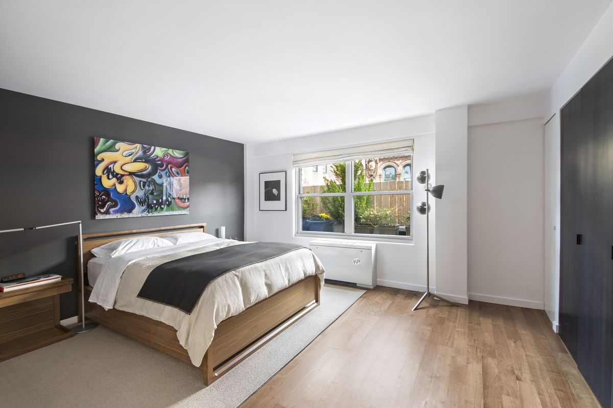 A bedroom with a medium-sized bed, hardwood floors, a large window, and black and white walls.