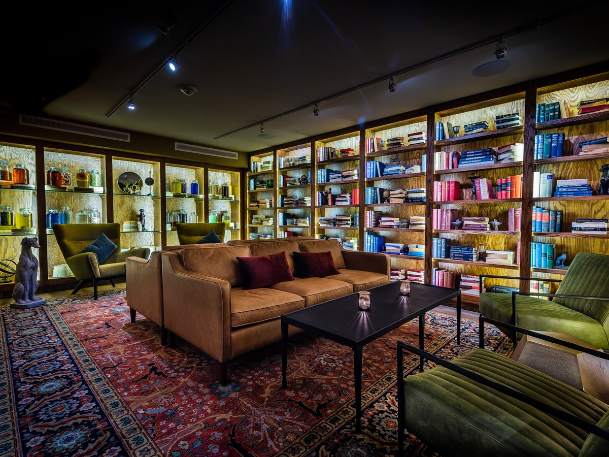 The interior of L'Annexe includes lounge seating and bookshelves holding bottles of infused liquor.