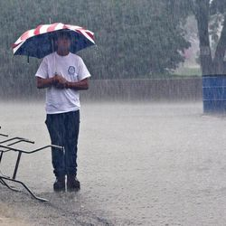 David Walker endures the rain from the remnant of Hurricane Isaac during opening ceremonies of the 29th Annual Labor's Family Day Picnic Saturday, September 1, 2012, at Columbian Park in Lafayette, Ind.