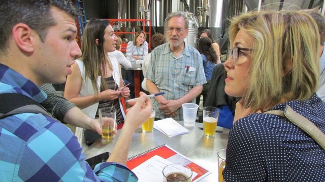 Indianapolis Public School Board President Mary Ann Sullivan (right) and special assistant to the superintendent Joe Gramelspacher (left) work on an answer with John Loflin of the Black and Latino Policy Institute (center) Education Trivia Night at Sun King Brewery sponsored by Chalkbeat and WFYI Public Media.