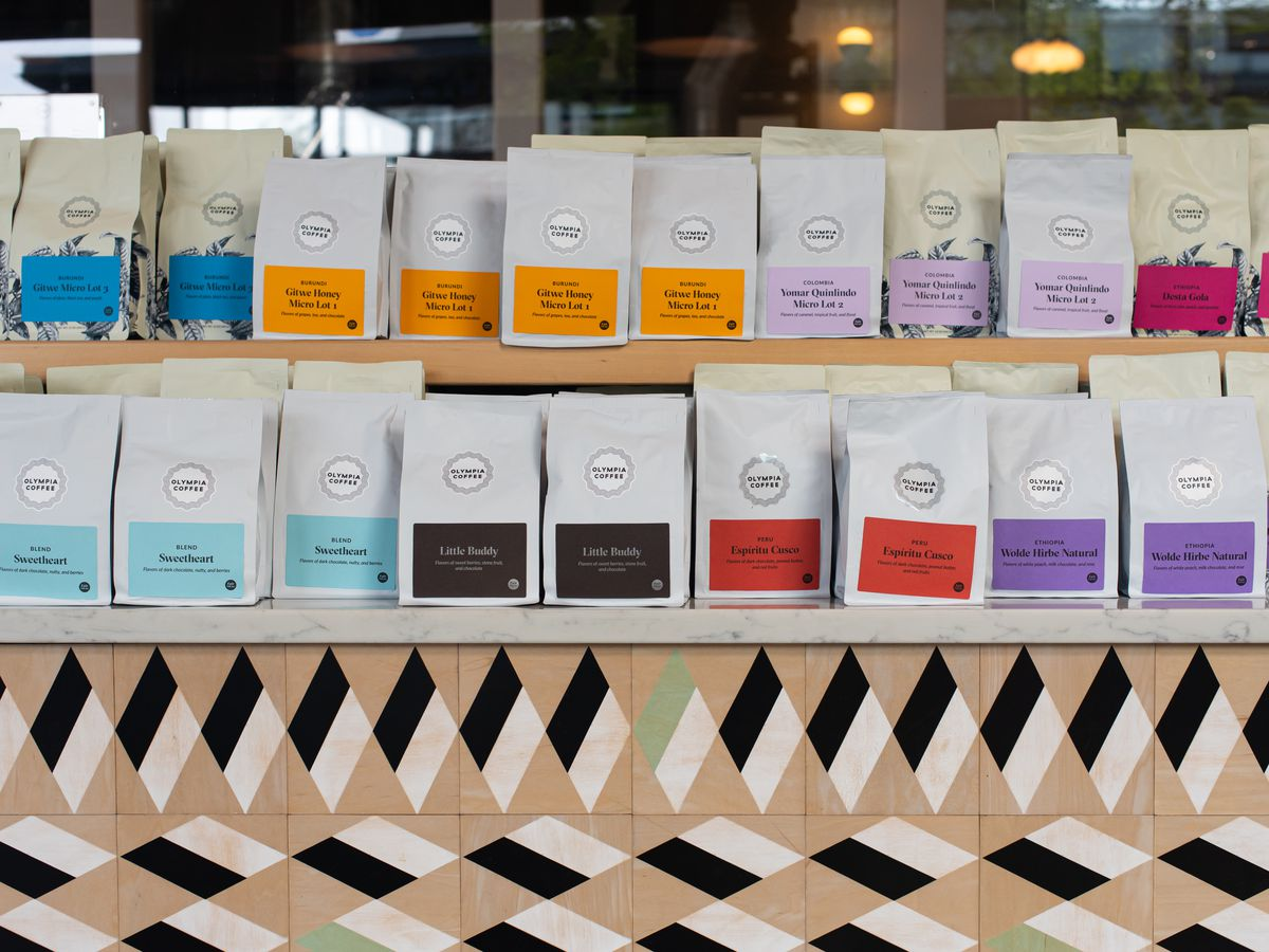 Shelves stocked with bags of Olympia Coffee roasts
