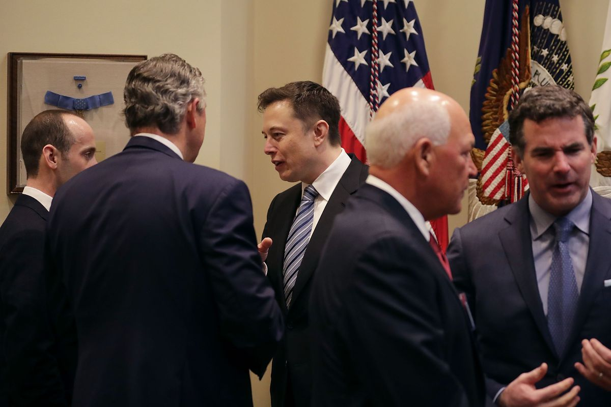 White House Senior Advisor Stephen Miller (L) and Klaus Kleinfeld of Arconic visit with Elon Musk (C) of SpaceX before a meeting with U.S. President Donald Trump in the Roosevelt Room at the White House January 23, 2017.