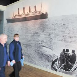Two workers at Belfast Titanic pass a wall print of the last known photograph of Titanic on display at the new tourist attraction in Belfast, Northern Ireland, on Wednesday, March 29, 2012. The wall photo taken on April 11, 1912, shows Titanic steaming away from Queenstown, Ireland, bound for New York.