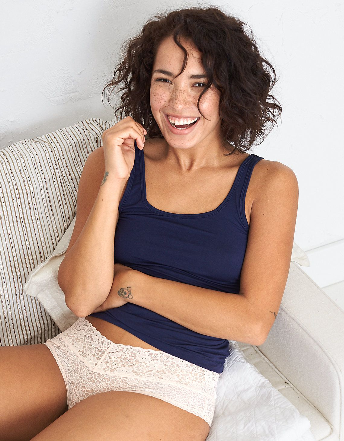 A model in a tank top and lace underwear