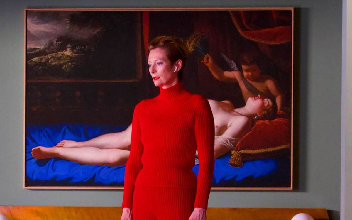 tilda swinton stands in front of a large painting