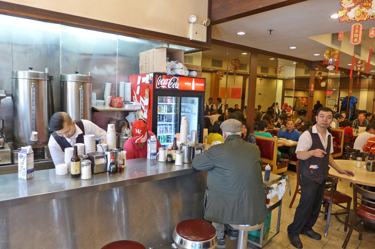 A man sits on a red bar stool at a coffee counter with one waiter behind the counter