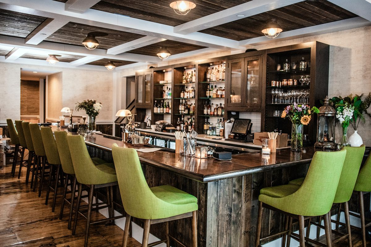 A photo of a bar with green bar seats, a wooden bar counter, and a wooden cabinet in the back that holds all the liquor.