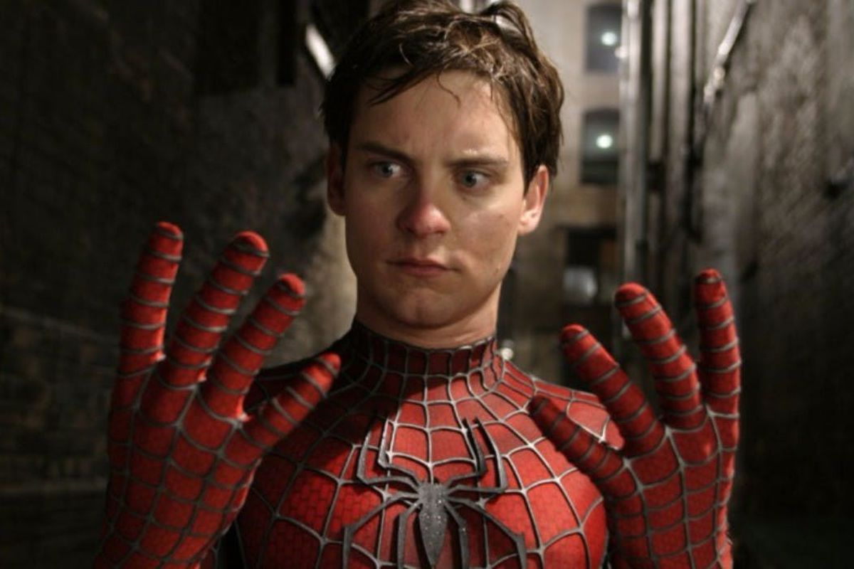 Tobey Maguire as Spider-Man looking at his hands with his mask off