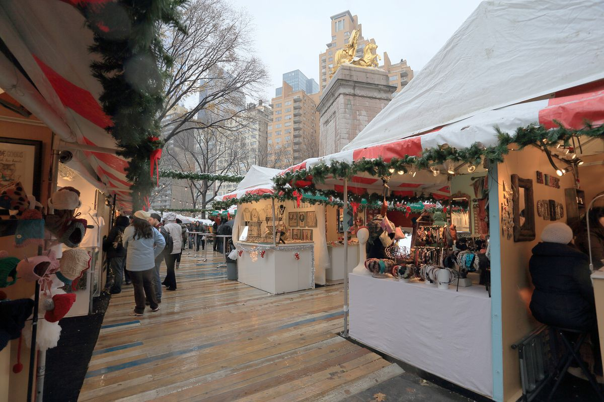 A holiday market in New York City. There are various market stalls with wares. Each stall is decorated with garlands. There are tall city buildings in the background.
