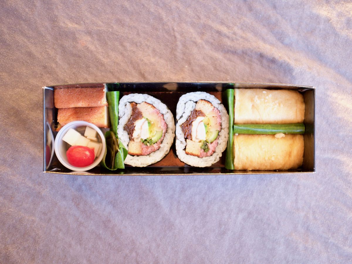 From above, a long rectangular segmented box with two large cut maki rolls and other dishes