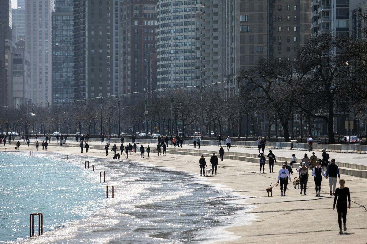 Residents enjoy the warm weather with a stroll along the Lakefront Trail near Oak Street Beach, Wednesday afternoon, March 25, 2020, in Chicago, despite a stay-at-home order from Illinois Gov. J.B. Pritzker during the coronavirus pandemic.