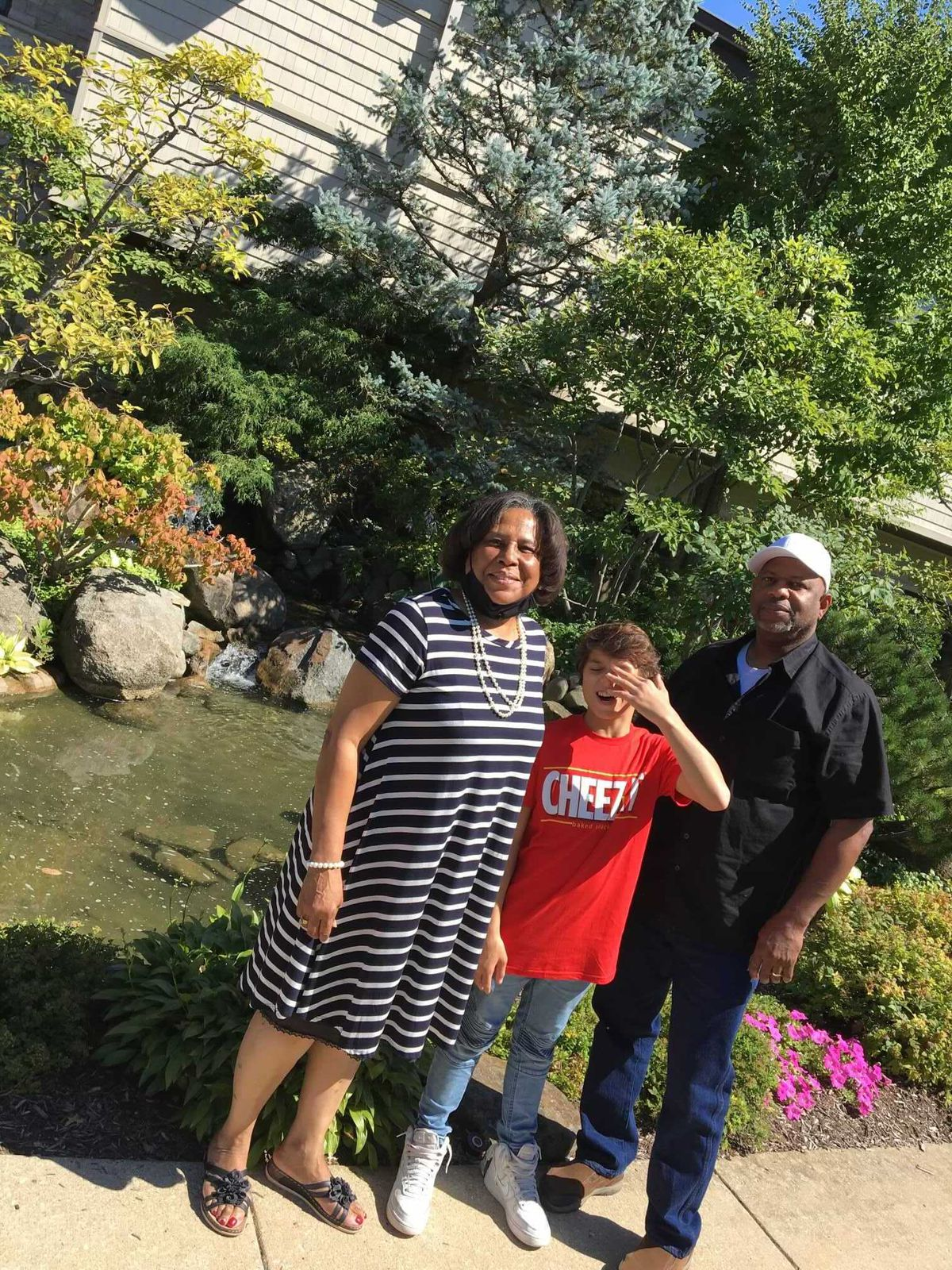 (Left to right) Yvonne Bailey poses for a portrait with her adopted son David and her husband, Terry Bailey in front of trees and a small pond on a sunny day.
