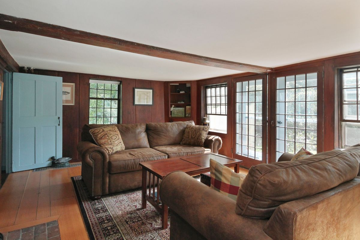 Two leather couches sit in front of a wooden coffee table, on a rug with pine floors. Brick walls are interrupted by windows.