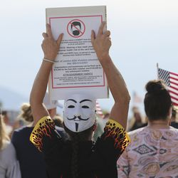 A demonstrator holds a against sign wearing a face mask during a rally at the Capitol in Salt Lake City on Thursday, June 25, 2020. About 100 people decried the possibility of increased coronavirus restrictions.