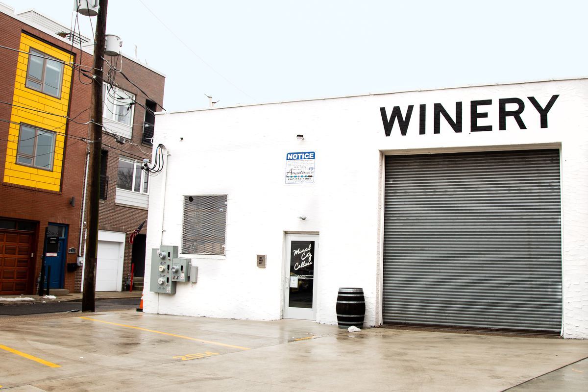 a white building that says winery on the front on a city street