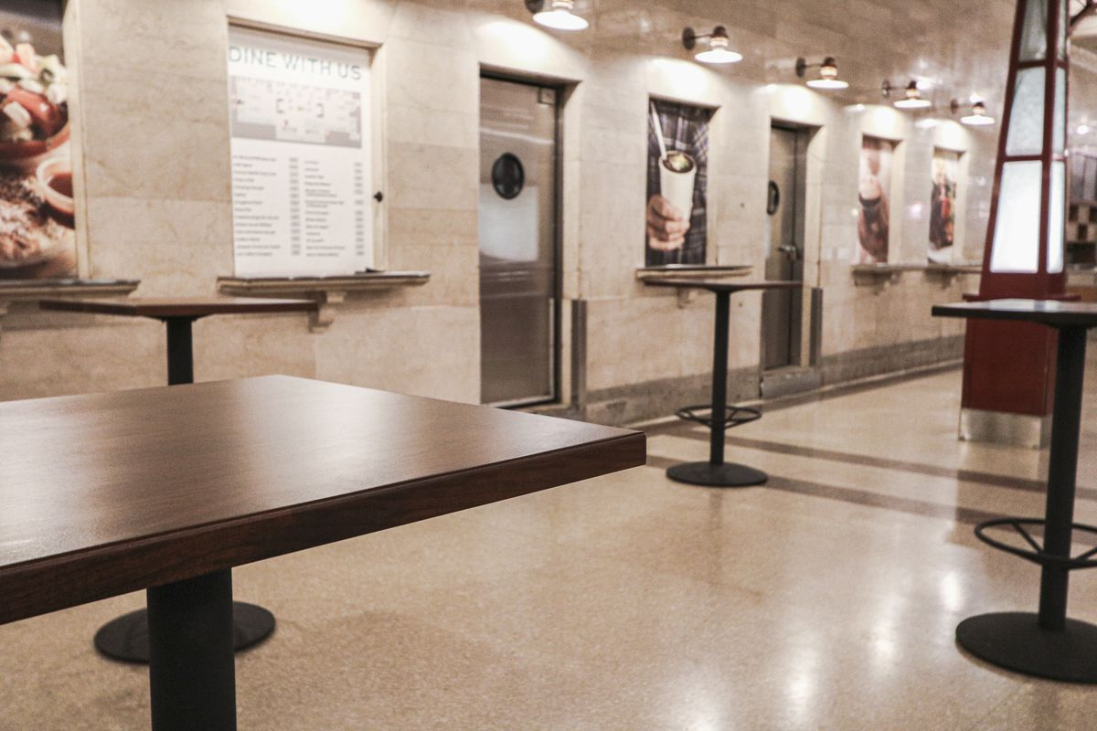 Two rows of hightop tables without chairs in an underground food court