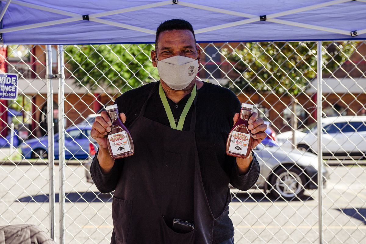 A man in a mask holds two bottles of barbecue sauce at My People's Market.