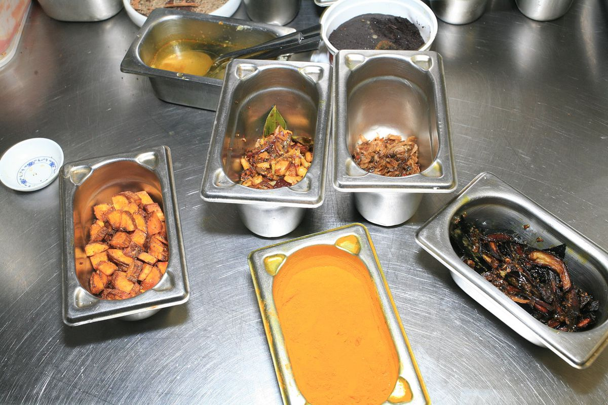A set of metal gastros, from left-to-right filled with ash plantain; dry-fried cashew nuts; balchan; turmeric; and caramelised aubergine