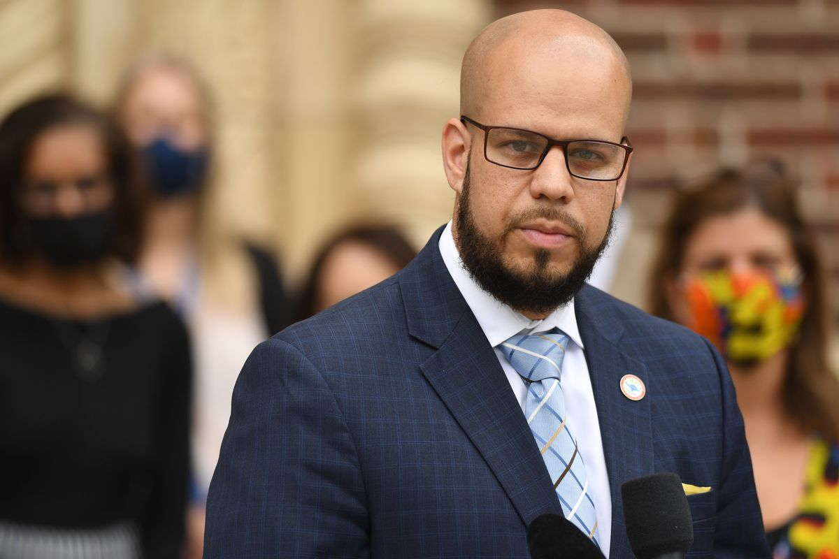 Dr. Alex Marrero, wearing a dark checkered suit jacket, white shirt, blue striped tie and a lapel pin.
