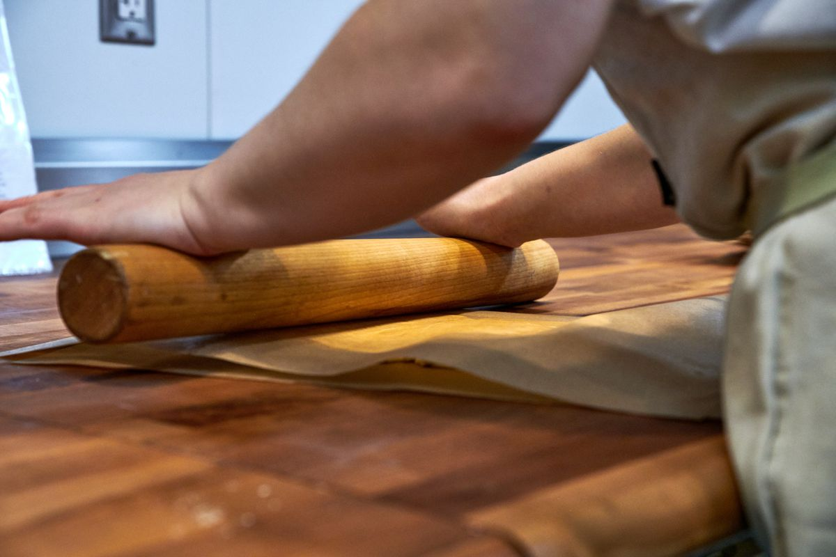 Suda holds both palms flat on a rolling pin, rolling out a sheet of butter between two pieces of parchment paper.