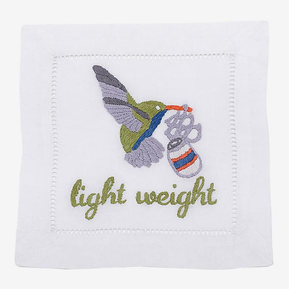 """A napkin embroidered with a hummingbird carrying a beverage can in its beak and the words """"light weight"""""""