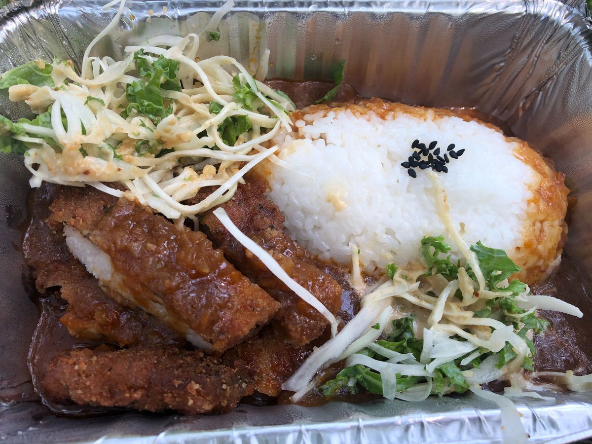 A foil takeout container with rice, chicken, curry, and a cabbage slaw inside