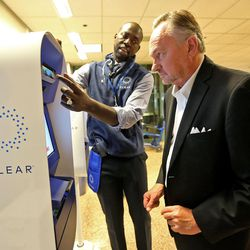 Alioune Fall, a CLEAR ambassador, shows Rex Falkenrath how to scan his iris while signing up for a new biometric, fee-based service that allows travelers to move past manual ID verification lines by using fingerprints and iris scans, at the Salt Lake City International Airport in Salt Lake City on Wednesday, July 12, 2017.