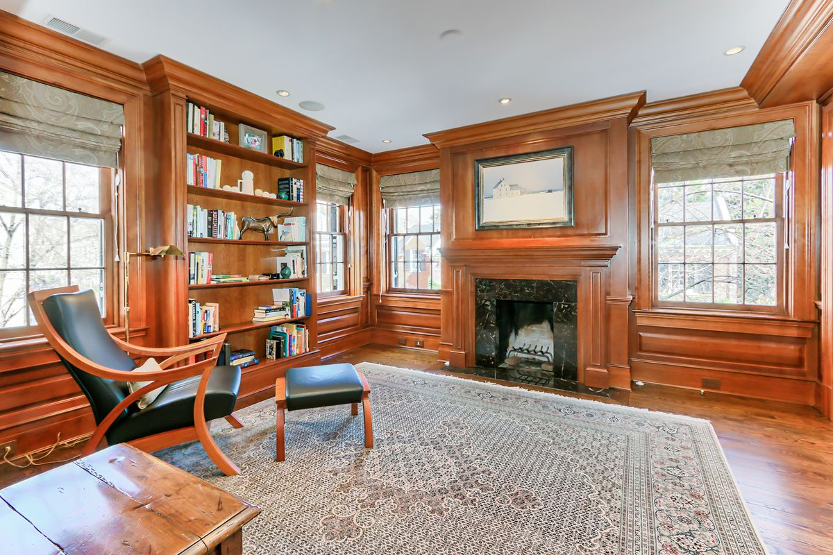 A library with a fireplace and wood-paneled walls.