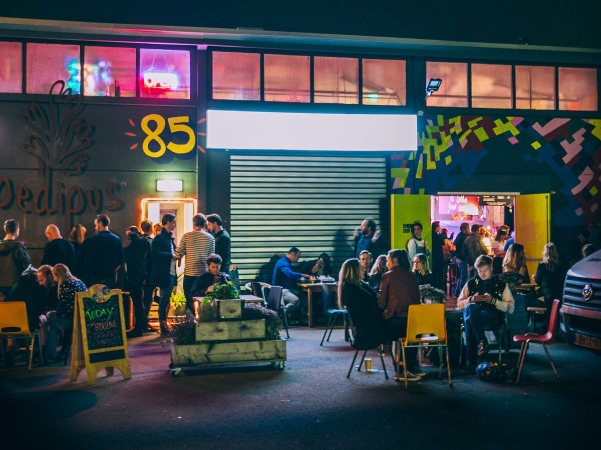 An industrial exterior with neon light pouring out of the warehouse-like space inside, and a large crowd gathered outside standing around open doorways or lounging on patio chairs.