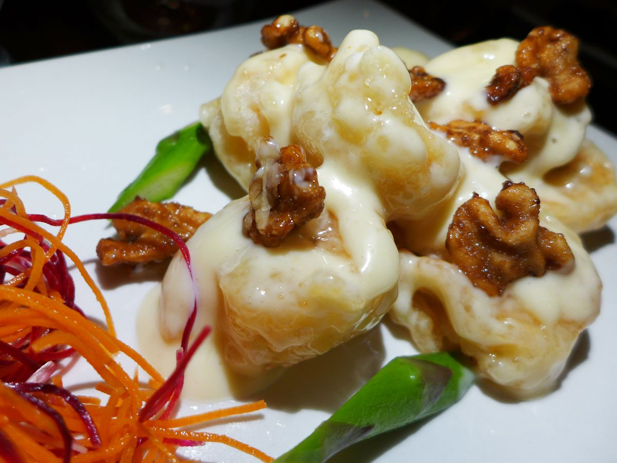 Four shrimp glazed with white sauce and a sugary walnut on top of each.