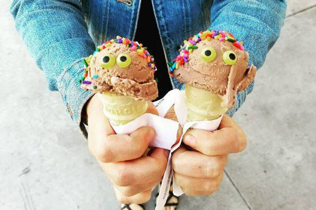 A young customer holds two Bruster's Real Ice Cream cones, upgraded with candy eyes.