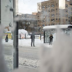 Seen through a bus stop shelter, commuters wait for a bus in the Edgewater neighborhood, Tuesday morning, Feb. 16, 2021, after a snowstorm dumped over a foot of snow in Chicago starting Sunday night. Snow is expected to continue to fall until Tuesday night.