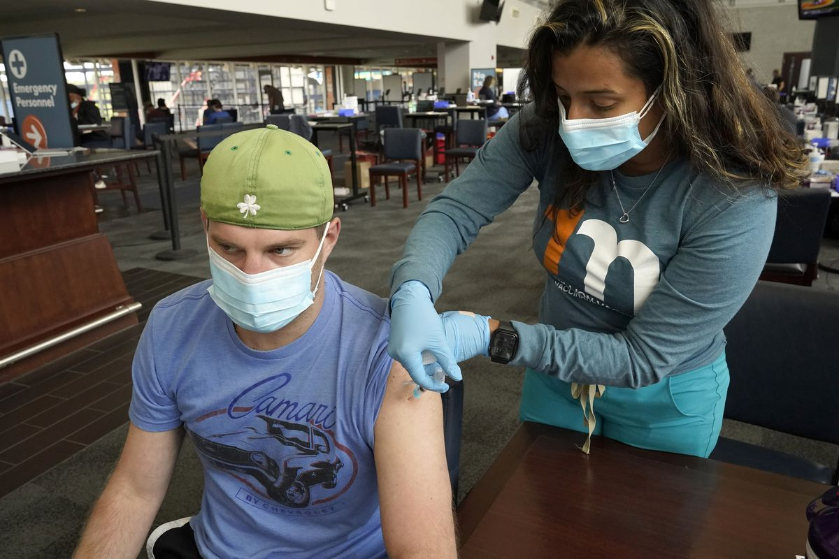 Kevin Fisher, of Quincy, Mass., left, receives his second shot of Moderna COVID-19 vaccine from RN Katherine Francisco, of Avon, Mass., right, at a mass vaccination clinic, Wednesday, May 19, 2021, at Gillette Stadium, in Foxborough, Mass.
