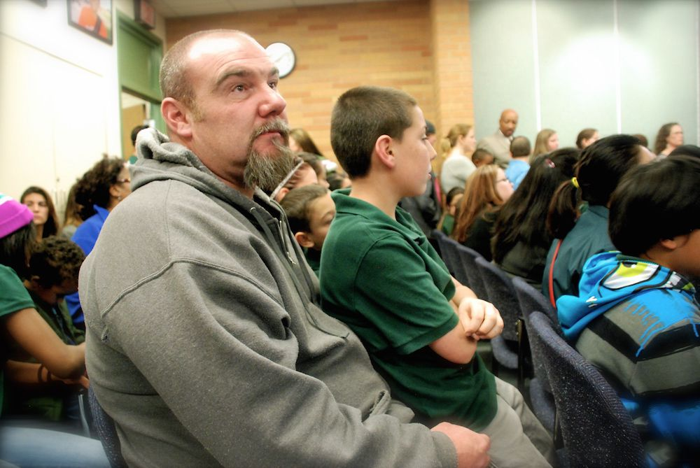 Donny Wright, left, and his son, Trenton Wright, 12, were among the 200 AXL Academy charter school supporters who packed an Aurora Public Schools Board of Education meeting earlier this month. AXL Academy has enough money to operate through January. It's requesting an 18-month charter extension and loan from the APS.